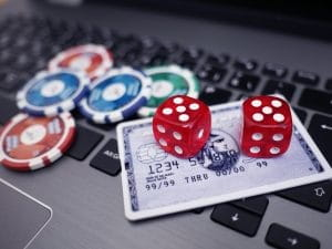 Jetons, Würfel und Kreditkarte auf der Tastatur eines Laptops.