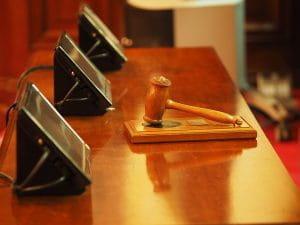 Richterhammer auf hölzernem Richterpult vor drei verschiedenen Displays.