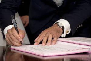 Mann unterzeichnet in einem Buch.