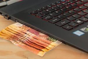 Mehrere Geldscheine stecken im Laufwerk eines Laptops.