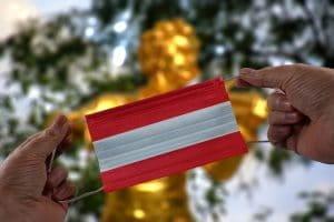 Corona-Schutzmaske in österreichischer Flaggenoptik in den Händen eines Mannes.
